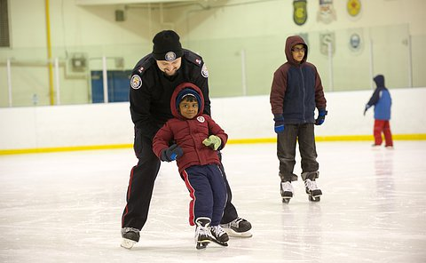 An officer on skates helps a little boy by holding him up on and pushing him on an indoor ice rink.