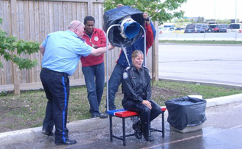 A woman in TPS uniform sits and has water dumped over her by three men