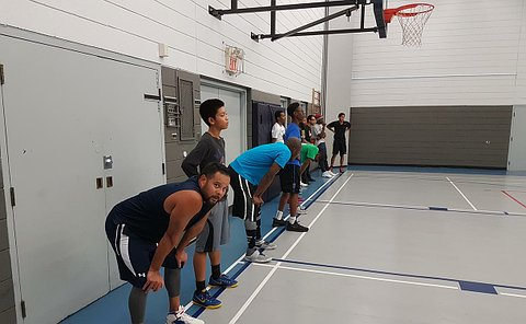Men and boys lined up in a gym