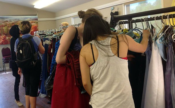 Several high-school students looking through a selection of dresses