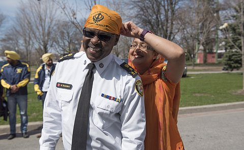 TPS Chief Saunders and event coordinator tying a scarf on the Chief.