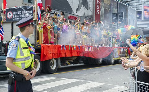 TPS Auxiliary Officer standing watching the crowd at the 2014 World Pride Parade. A truck with parade participants passes in the background.