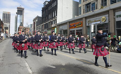 A group of men in TPS uniform and kilts playing bagpipes marching down a street