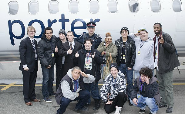 A group of people in front of an airplane with the word Porter on side