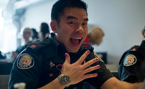 A uniformed male officer smiling and holding up his hand to show his pink painted nails.
