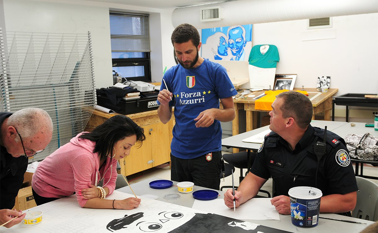 A man stands over two men in TPS uniform and a teenage girl seated at a table holding brushes over an artistic work