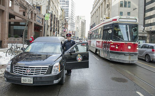 A man in Toronto Police uniform stands by a hearse with a TPS logo on the door