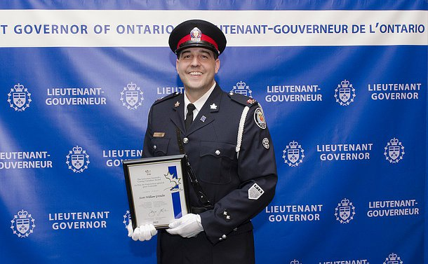 A man in TPS uniform holds a plaque