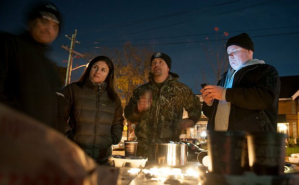 Four people gathered around a bench with candles on the table. Three people are visible and one is blurry, it is nighttime.