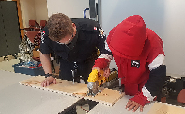 A man in TPS uniform and a child using a jigsaw on a piece of wood