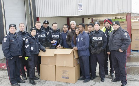 A group of men and women in TPS uniform with several young people with boxes in front of them