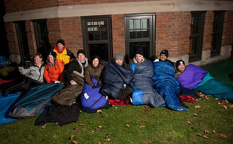 About 10 people curled up in sleeping bags but sitting up against a brick building look at the camera. Some are smiling, some are not.