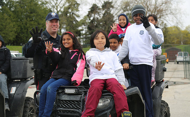 A group of kids on an ATV holding up four fingers with a man in TPS uniform
