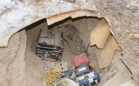 A generator, gas can, wire in a hole