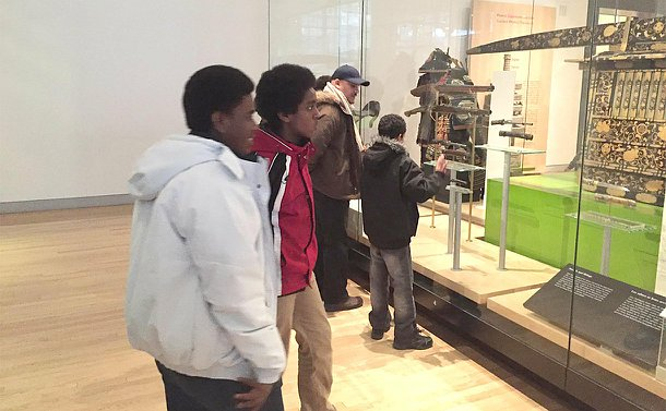 Two groups of two look at artifacts in a large glass case