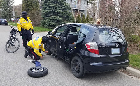 Two men in uniform changing tire