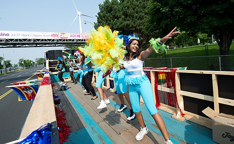 A few young women in blue costume dance on a float.