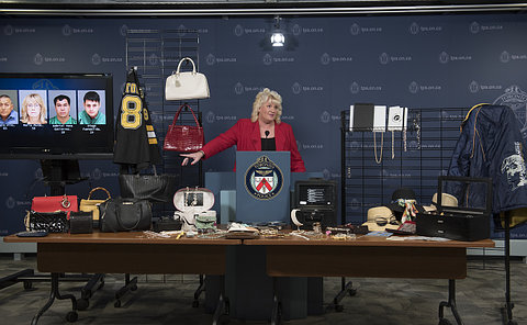 A woman at a podium beside racks of clothing and tables of handbags, jewellery and watches