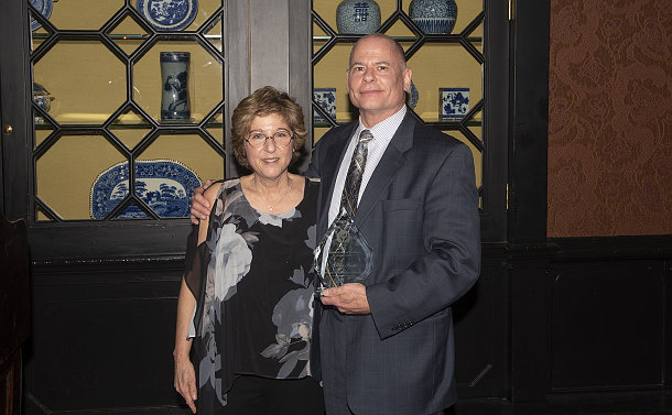A man and a woman holding a glass award