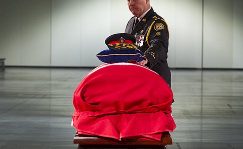 A man in Toronto Police uniform touches a flag draped casket
