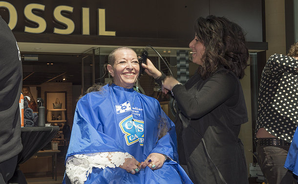 A woman has her head shaved by another woman