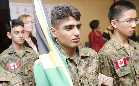 Three teenage boys in military uniform looking forward