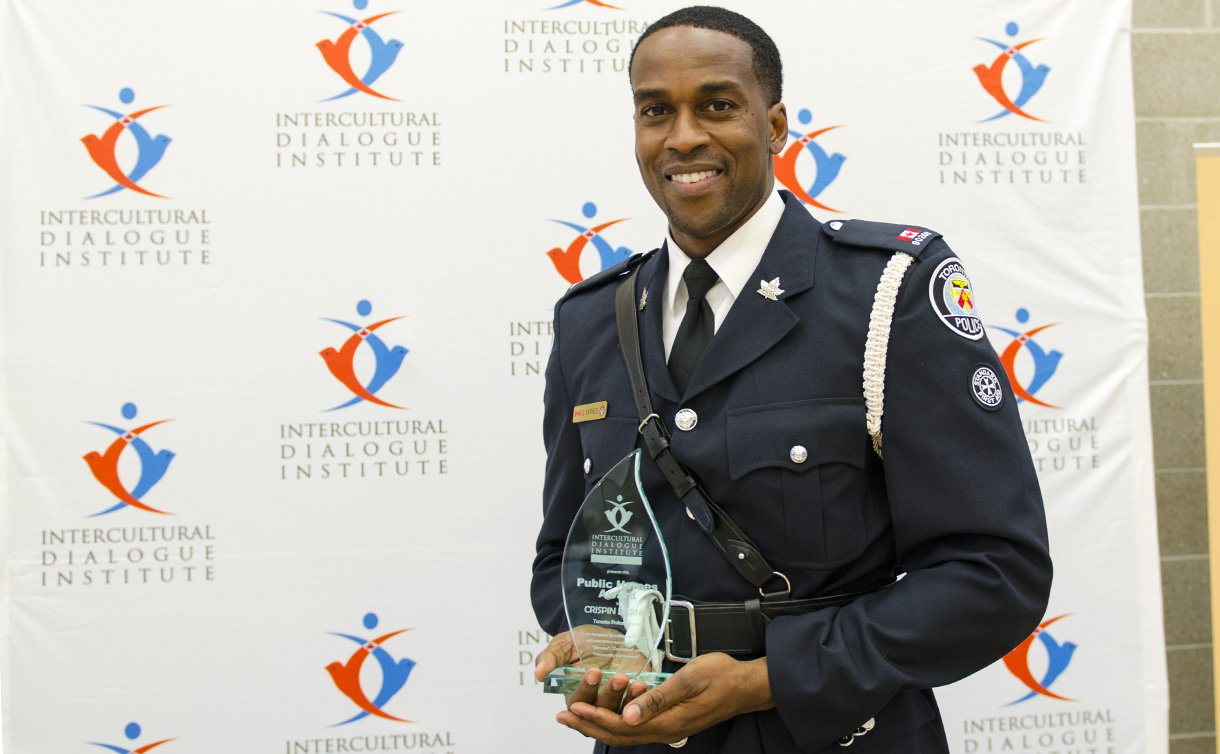 A man in uniform with an award trophy in his hands.