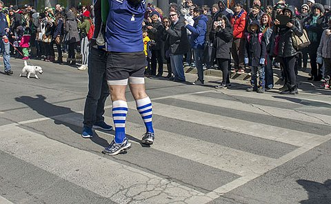 Two men hold up another man in rugby uniform holding his arms up to catch a ball