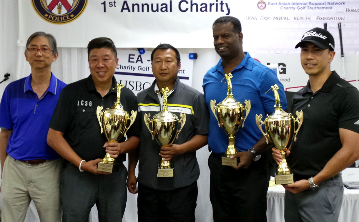 Four men folding trophies smiling for the camera.