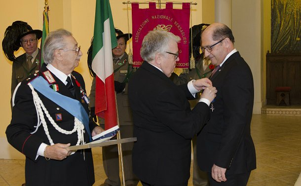 Three men, one pinning a medal to another's lapel