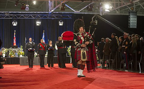 A piper leads a group of people in uniform and casket down a large aisle on red carpet