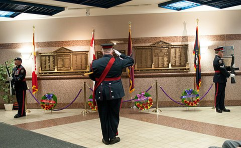 A man in uniform salutes in front of a wall with inscribed with names as two men in uniform bow their heads holding rifles