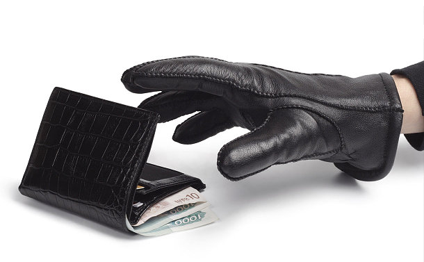 Stock photo of a hand wearing a glove reaching for a wallet