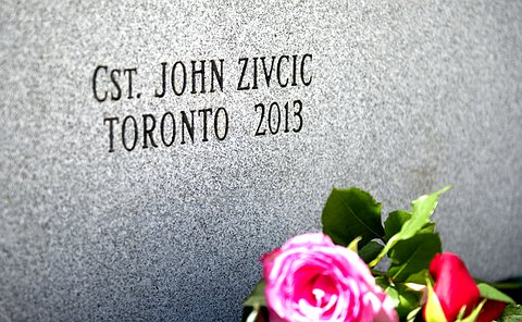 Cst. John Zivcic Toronto 2013 etched into granite wall with flowers at base of wall
