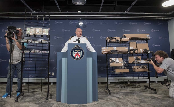 A man in TPS uniform at a podium beside metal racks holding Canadian money and firearms. A video and still camera on either side