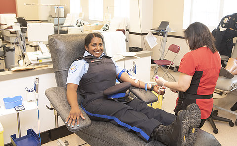 A woman in TPS parking uniform giving blood