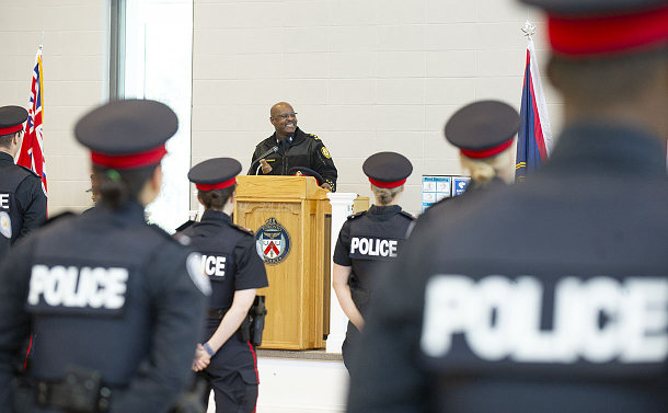 A man in TPS uniform at a podium in front of others in TPS uniform