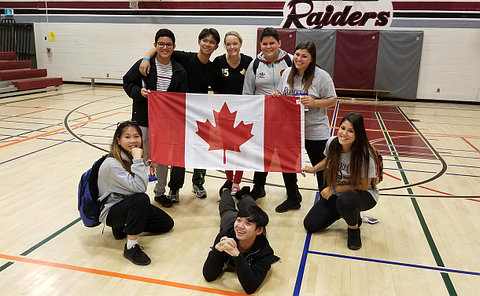 Teenagers with woman holding Canadian flag