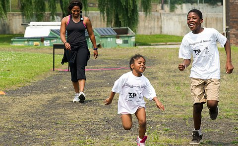 Two young children are in the foreground running, while a plainclothes officer is in the background catching up to them.