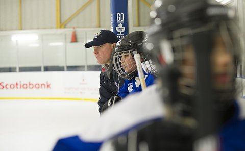 A man in a TPS baseball cap leans over boards beside children in hockey equipment