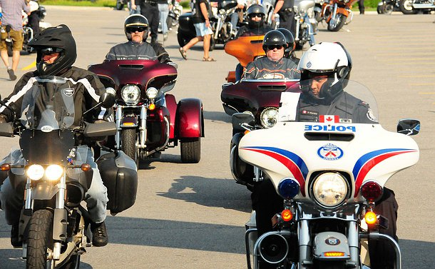 A man in TPS uniform on a TPS motorcycles accompanied by other men nearby on motorcycles