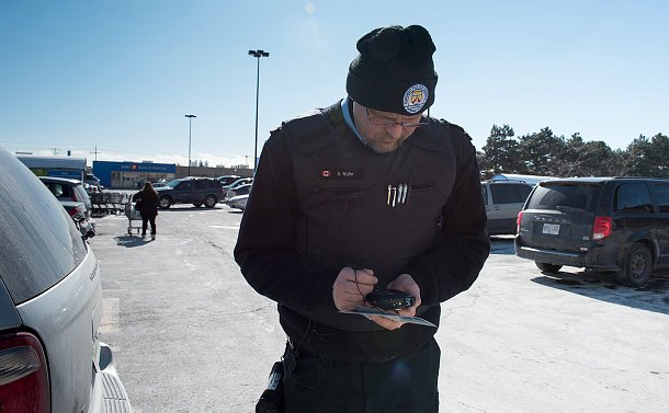A man in parking enforcement uniform looking down typing