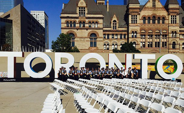 A large group of people in TPS Auxiliary uniform in front of a Toronto sign