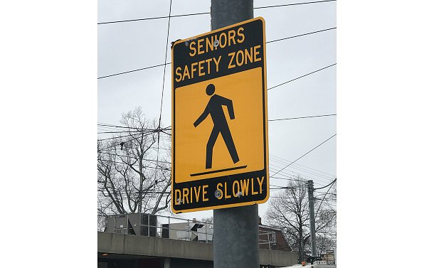A sign with a symbol of a person walking with words: Senior Safety Zone Drive Slowly