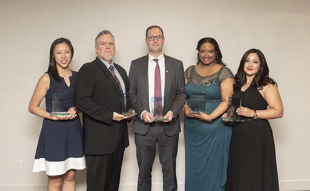 A group of people holding awards