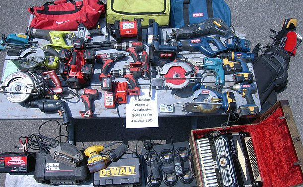 A wide assortment of power tools laid on the ground along with an accordion in a box