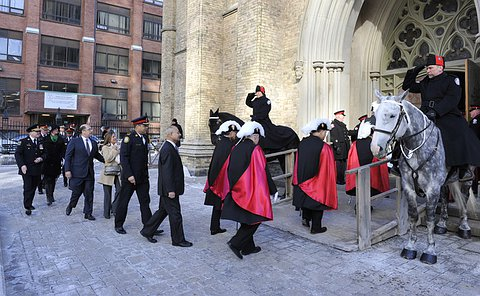 People in TPS uniform enter a church with people in Knights of Columbus uniform as well as others in formal attire