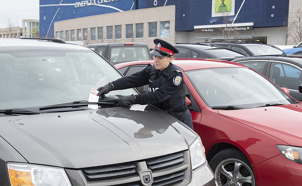 A woman in TPS uniform putting a flyer under a windshield wiper