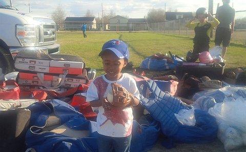A boy holds a softball in a baseball glove