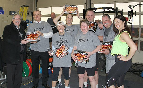 "A group of people in workout gear in a gym holding DVD boxes marked ""Insanity"""